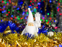 Santa figure with Christmas balls, tinsel on blurred lights background Stock Image
