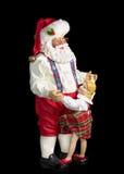 Santa Figurine som dansar med lilla flickan, på svart bakgrund Royaltyfria Bilder