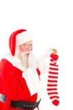 Santa filling a stocking on white Royalty Free Stock Photos