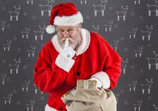 Santa with finger on lip holding christmas gifts Stock Photography