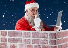 Santa with finger on lip using laptop Stock Image