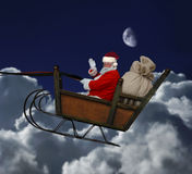 Santa in Flight. Santa in his sleigh flying through a nighttime cloudscape Stock Photos