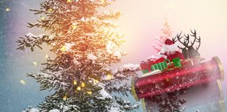 Composite image of santa flying his sleigh. Santa flying his sleigh against snow covered trees during winter Stock Photo