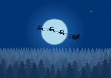 Santa flying through the night sky under the christmas forest. Santa sleigh driving over woods near big moon in night. Stock Photo