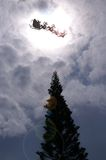 Santa flying sky. Pine tree Stock Photo