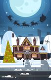 Santa Flying In Sledge With Reindeers In Sky Over Village Houses, Merry Christmas And Happy New Year Banner Winter Royalty Free Stock Photo