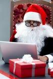Santa fonctionnant avec l'ordinateur Photographie stock libre de droits
