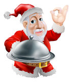 Santa with food. A cartoon happy Santa  doing a chef's perfect sign with his hand and holding a covered metal plate of food Stock Photography