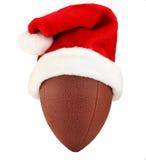 Santa Football. American football wearing a red and white Santa Hat Stock Images