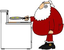 Santa frying eggs Royalty Free Stock Photography
