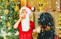 Santa fun. Merry Christmas. Santa - funny child picking cookie. Santa Claus takes a cookie on Christmas Eve as a thank