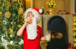 Santa fun. Merry Christmas. Santa - funny child picking cookie. Santa Claus takes a cookie on Christmas Eve as a thank