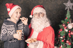 Santa and funny boy with cookies and milk at Christmas. Santa looking at camera and funny boy laughing and holding cookies and milk at Christmas. Concept of Stock Photos