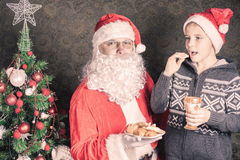 Santa and funny boy with cookies and milk at Christmas. Santa looking at camera and funny boy laughing and holding cookies and milk at Christmas. Concept of Royalty Free Stock Photography