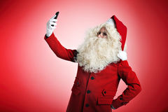 Santa with gadgets in hands. Fitted Santa in fashionable coat takes selfie on his new mobile smart phone ,  on red christmas background Stock Image
