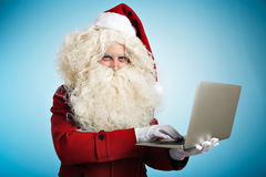 Santa with gadgets in hands. Santa looking at camera wisely and texting something on portable laptop he holds on his hand,  on blue background Computer repairing Royalty Free Stock Photos