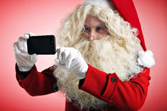 Santa with gadgets in hands Royalty Free Stock Photography
