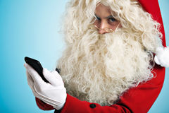 Santa with gadgets in hands. Unfocused Santa looking at camera abore his golden round glasses and holding focused smartphone in his hand on foreground Stock Photos