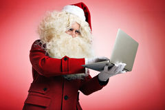 Santa with gadgets in hands. Santa in white gloves quickly types mail or programming code on his portable laptop, hacking web site and fixing bugs.  on red Stock Photos