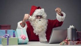 Santa gaie se reliant à son ordinateur portable Photo libre de droits