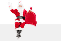 Santa gesturing happiness seated on a panel Royalty Free Stock Images
