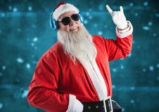 Santa gesturing while listening music on headphones Stock Photography