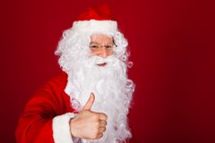 Santa gesturing thumb-up. Portrait of happy santa gesturing thumb-up on red background Royalty Free Stock Images
