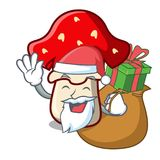 Santa with gift amanita mushroom mascot cartoon Royalty Free Stock Photo