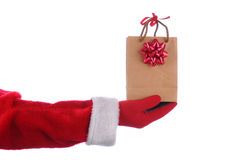 Santa with gift bag. Santa Claus outstretched arm with a gift bag in his hand. Horizontal format over a white background Royalty Free Stock Photos