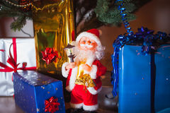 Santa and gift packs. Little Santa with the small torch on the background gift package stock image