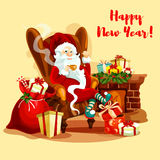 Santa with gifts sitting near fireplace. Santa Claus resting with cup of tea near fireplace, decorated with holly berry garland, gift and present boxes, candy Royalty Free Stock Image