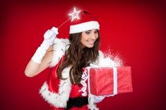 Santa girl adding magic to Christmas present. Santa woman adding little magic to Christmas present Stock Photo