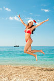 Santa girl in a bathing suit and hat against the sea. Royalty Free Stock Images