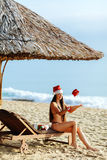 Santa girl on the beach with christmas gift. Santa girl in bikini on the beach throwing christmas gift in hands with smile. Happy new year girl in bikini on the Stock Image