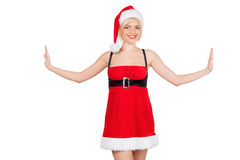 Santa girl. Beautiful young woman in Santa costume stretching out her hands and smiling while standing isolated on white Royalty Free Stock Image