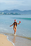 Santa girl in bikini on the beach  resort  with present Stock Photo