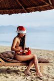 Santa girl in bikini  unpacking christmas gift Royalty Free Stock Photo