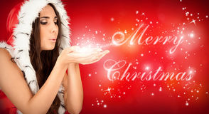 Santa girl blowing Merry Chrsimas text royalty free stock photo
