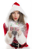 Santa girl blowing snow. Beautiful Santa girl blowing snow off the Christmas gift box in her hand Royalty Free Stock Image