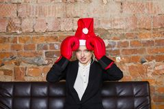 Santa girl businesswoman with notebook and laptop at loft office on leather couch in suit with boxing gloves. Stock Photography