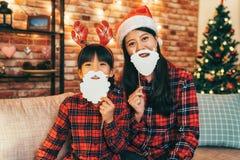 Santa girl and child with deer on head having fun stock photo