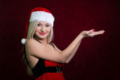 Santa girl in Christmas cap gestures palm up Royalty Free Stock Photo