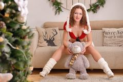 Santa girl in Christmas costume with cute teddy bear sits on sofa Royalty Free Stock Photography