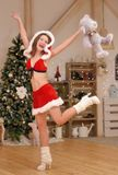 Santa girl in Christmas costume jumps with cute teddy bear Royalty Free Stock Photos