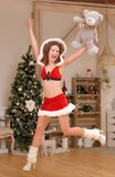 Santa girl in Christmas costume jumps with cute teddy bear Stock Photography