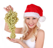 Santa girl in Christmas hat with bunch of grapes Stock Image