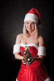 Santa girl with Christmas tree. Royalty Free Stock Photo