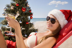 Santa girl in Christmas vacation on the beach. With a glass of martini Royalty Free Stock Images