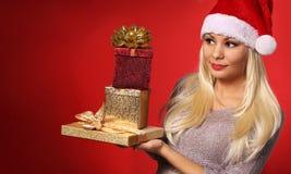 Santa Girl com as caixas de presente sobre o fundo vermelho Natal Imagens de Stock