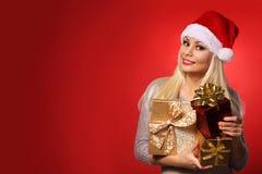 Santa Girl com as caixas de presente sobre o fundo vermelho Natal Imagem de Stock